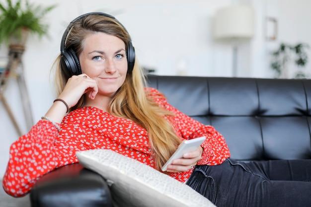 Gelukkige vrouw die aan muziek luistert die hoofdtelefoons draagt