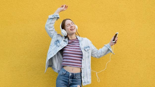 Gelukkige vrouw die aan muziek luistert