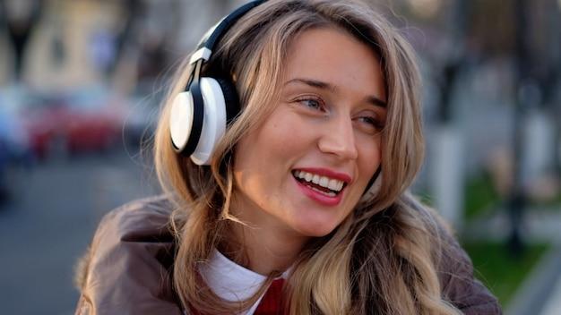 Gelukkige vrouw die aan muziek op draadloze hoofdtelefoons luistert