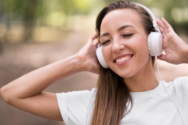 Gelukkige vrouw die aan muziek op haar hoofdtelefoons luistert