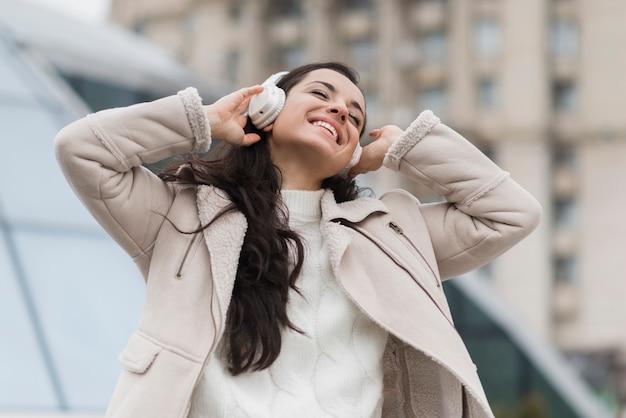 Gelukkige vrouw die aan muziek op hoofdtelefoons luistert