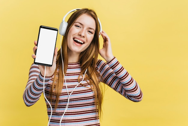 Gelukkige vrouw die aan muziek op telefoonmodel luistert