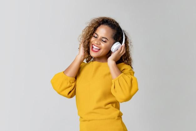 Gelukkige vrouw die aan muziek van hoofdtelefoons luistert