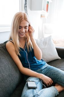 Gelukkige vrouw die aan muziek van mobiele telefoon thuis luistert