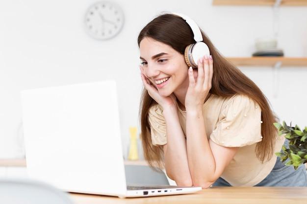 Gelukkige vrouw die aan muziek via hoofdtelefoons luistert