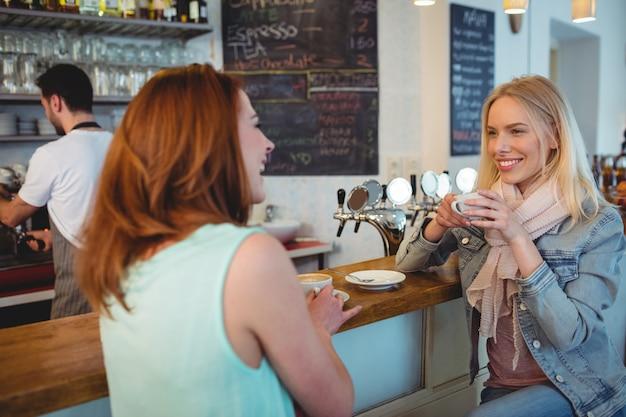 Gelukkige vrouw die aan vriend bij koffieteller spreekt