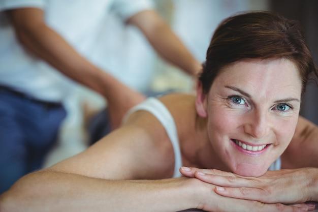 Gelukkige vrouw die achtermassage van fysiotherapeut ontvangt
