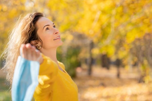 Gelukkige vrouw die beschermend masker buiten draagt. meisje met plezier in herfst park. vrijheid en pandemie coronavirus covid 19 concept