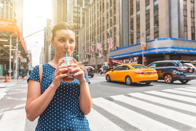 Gelukkige vrouw die bevroren koffie in new york drinkt