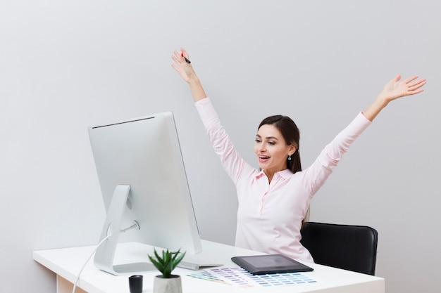 Gelukkige vrouw die bij bureau computer bekijkt