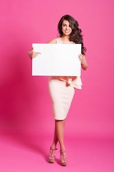 Gelukkige vrouw die bij leeg whiteboard toont
