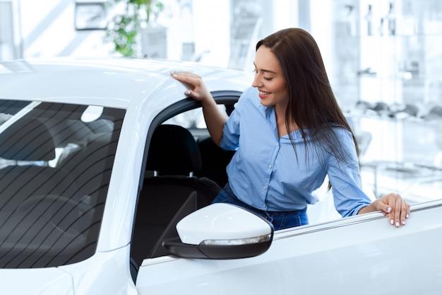 Gelukkige vrouw die binnen van een nieuwe auto krijgt gaat zij bij de lokale autosalon kopen