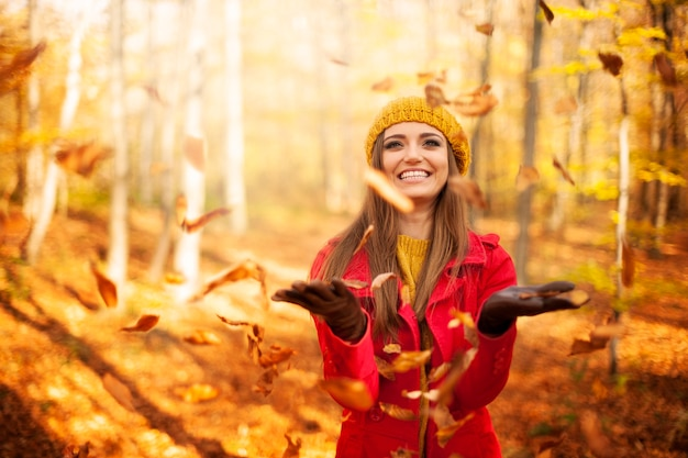 Gelukkige vrouw die bladeren werpt