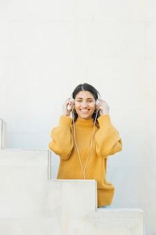 Gelukkige vrouw die camera bekijkt die hoofdtelefoons draagt