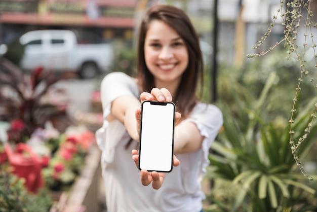 Gelukkige vrouw die cellphone met het lege witte scherm toont