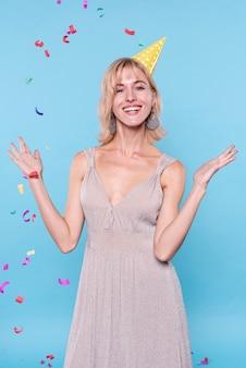 Gelukkige vrouw die confettien in de lucht werpt
