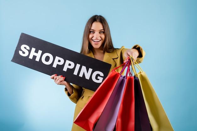 Gelukkige vrouw die copyspace zwarte het winkelen banner en kleurrijke die het winkelen zakken houden over blauw wordt geïsoleerd