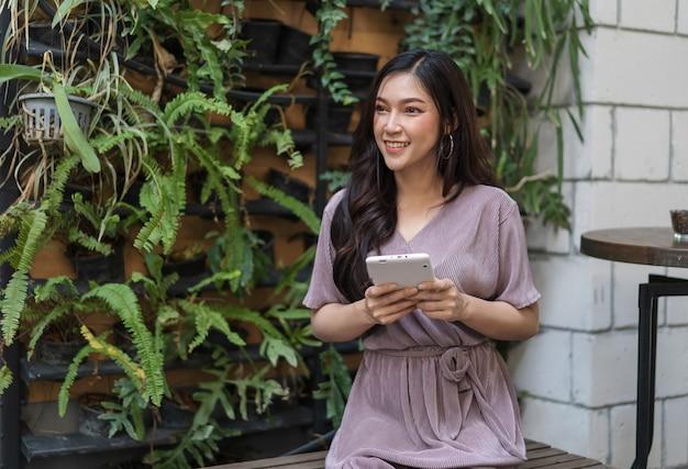 Gelukkige vrouw die creditcard gebruiken aan online het winkelen met tablet bij koffie