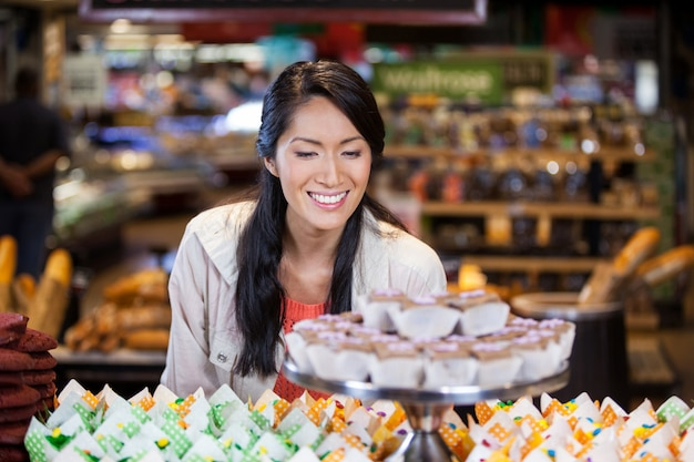 Gelukkige vrouw die cupcakes bekijkt