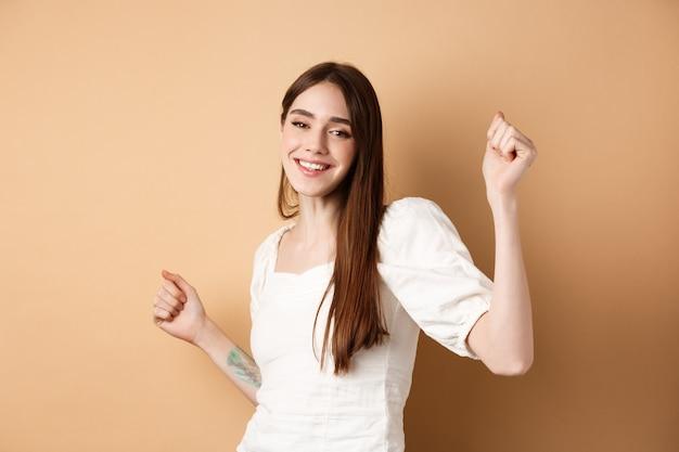 Gelukkige vrouw die danst en plezier heeft, sluit de ogen en lacht terwijl ze op een beige achtergrond staat