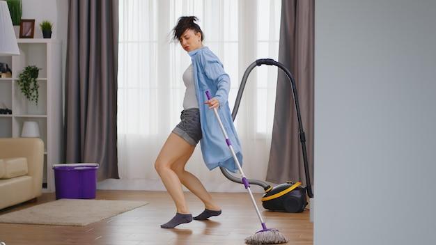 Gelukkige vrouw die danst terwijl ze het vloerhuis schoonmaakt met dweil