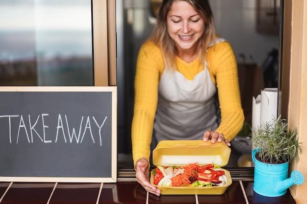 Gelukkige vrouw die de bestelling van afhaalmaaltijden biologisch voedsel in plastic vrij restaurant voorbereidt