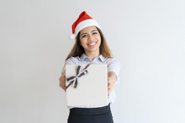 Gelukkige vrouw die de hoed van de kerstman draagt en giftdoos geeft