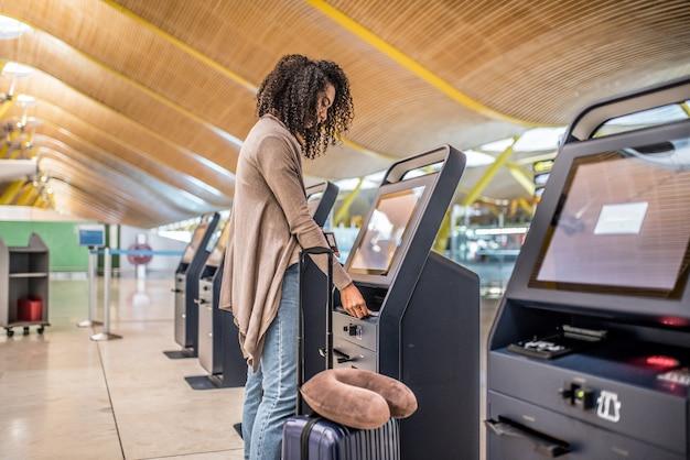 Gelukkige vrouw die de incheckmachine gebruikt op de luchthaven die de instapkaart krijgt.