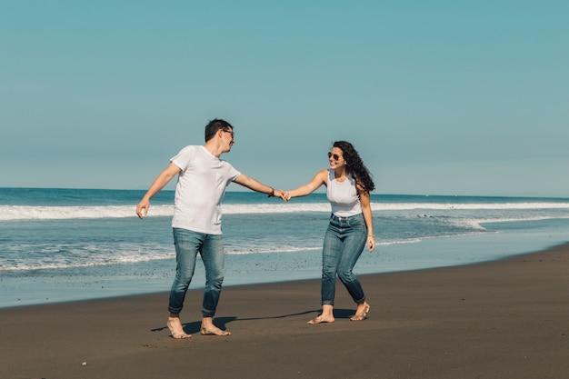 Gelukkige vrouw die de mens wenst te volgen aan water op strand
