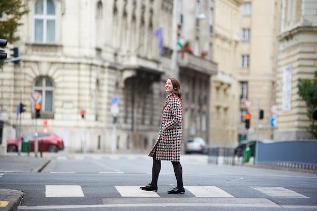 Gelukkige vrouw die de straat oversteken