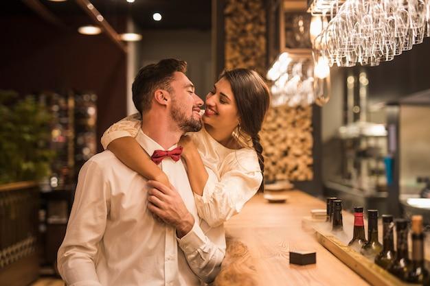 Gelukkige vrouw die de vrolijke mens koestert bij barteller