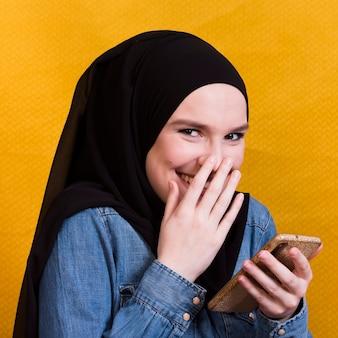 Gelukkige vrouw die denimoverhemd dragen die smartphone op heldere achtergrond gebruiken