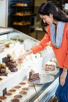 Gelukkige vrouw die desserts selecteert
