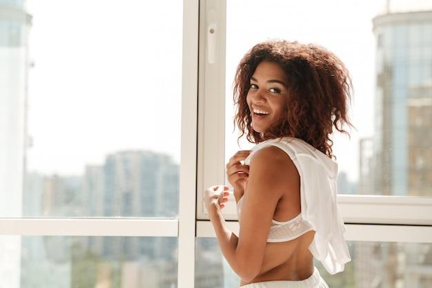 Gelukkige vrouw die dichtbij venster aan camera glimlachen