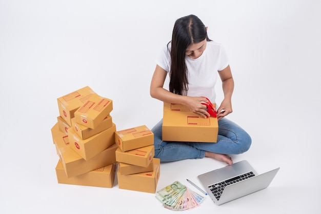 Gelukkige vrouw die dozen in online verkoop inpakken online het werkconcept