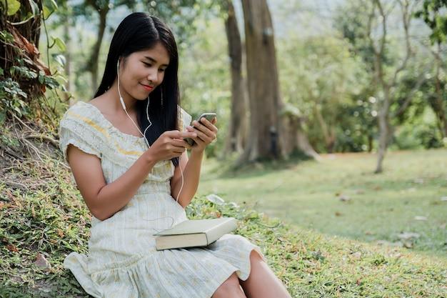 Gelukkige vrouw die dragend oortelefoons glimlachen die op park zitten die aan muziek op een smartphone luisteren