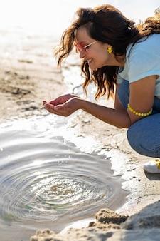 Gelukkige vrouw die duidelijk water in openlucht vinden