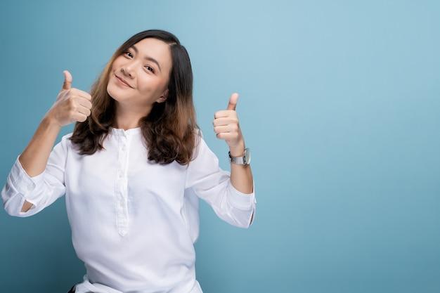 Gelukkige vrouw die duim toont die omhoog op achtergrond wordt geïsoleerd