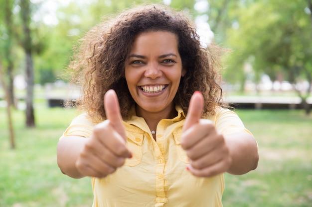 Gelukkige vrouw die duimen tonen en bij camera in park stellen