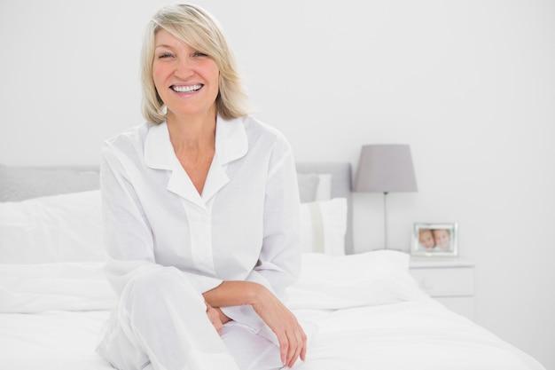 Gelukkige vrouw die dwars legged in haar slaapkamer zit