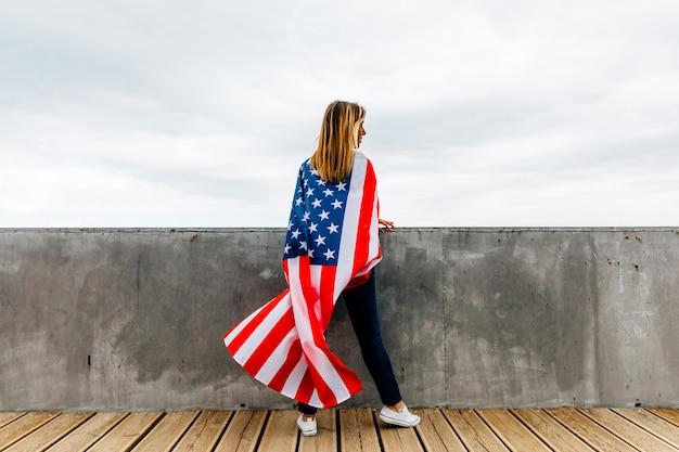 Gelukkige vrouw die een amerikaanse vlag houdt