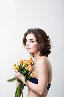 Gelukkige vrouw die een boeket van kleurrijke bloemen houdt.