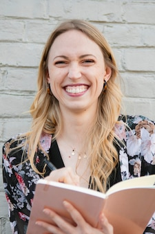 Gelukkige vrouw die een dagboek schrijft