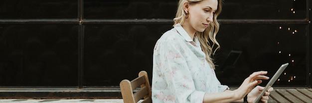 Gelukkige vrouw die een digitale tablet buitenshuis gebruikt