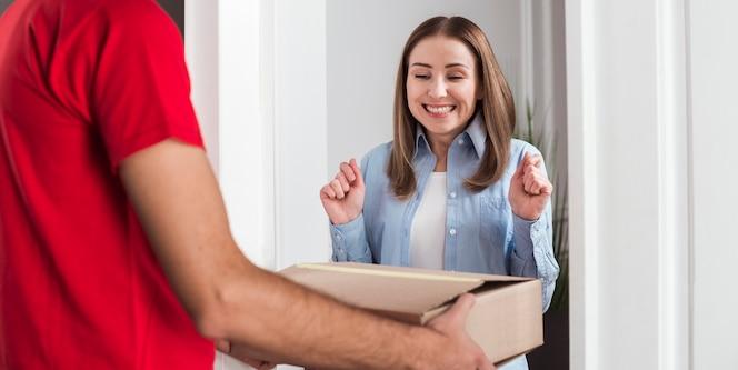 Gelukkige vrouw die een doos met haar aankopen ontvangt