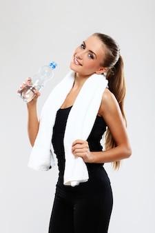 Gelukkige vrouw die een fles water houdt