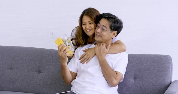 Gelukkige vrouw die een gele giftdoos geeft aan een man.
