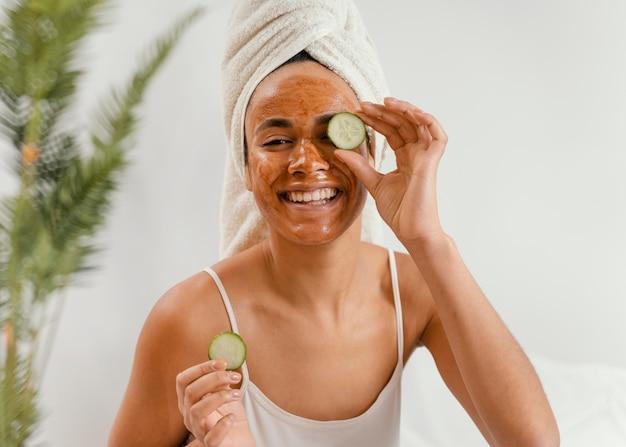 Gelukkige vrouw die een natuurlijk gezichtsmasker gebruikt