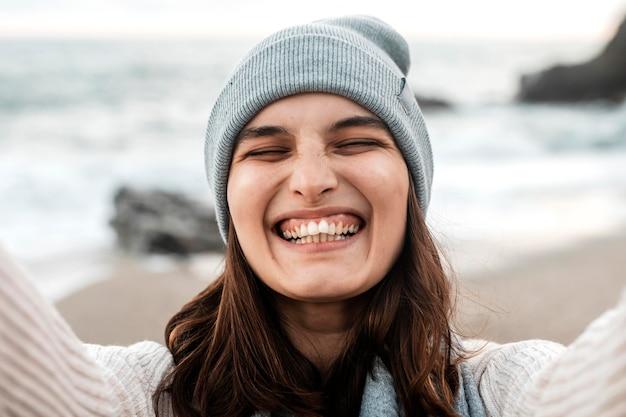 Gelukkige vrouw die een selfie op het strand neemt