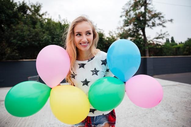 Gelukkige vrouw die een stel kleurrijke luchtballonnen buiten vasthoudt